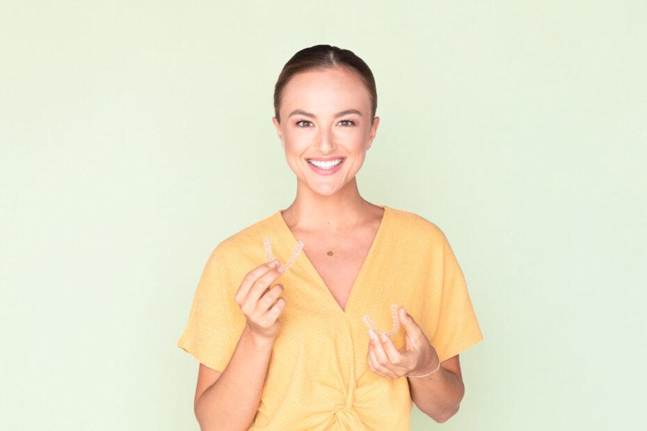 Patientin mit Retainer Schienen in der Hand vor mintgrünem Hiontergrund