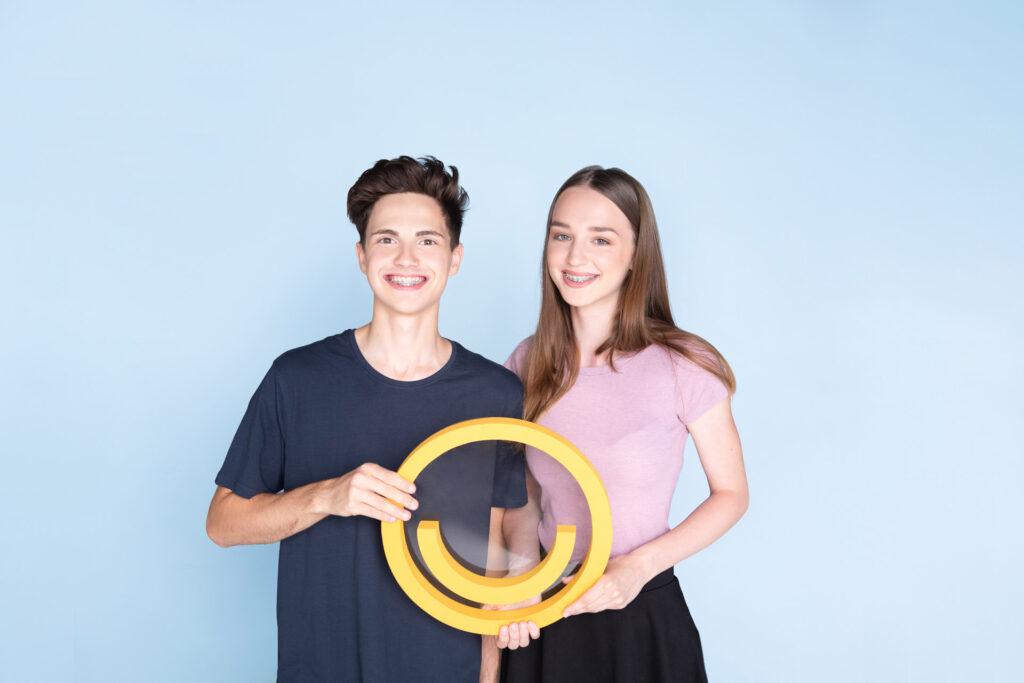 Ein Bub und ein Mädchen mit Gratis-Zahnspange von Prof. Jonke halten das Jonke-Smiley gemeinsam vor blauem Hintergrund.