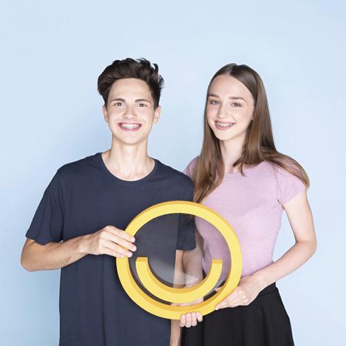 Zwei Patienten mit Zahnspange halten das Jonke-Logo