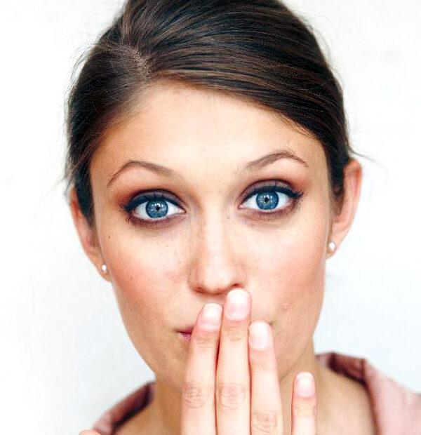 Frau mit Hand vor Mund weil die Zahnspange im Urlaub kaputt gegangen ist.