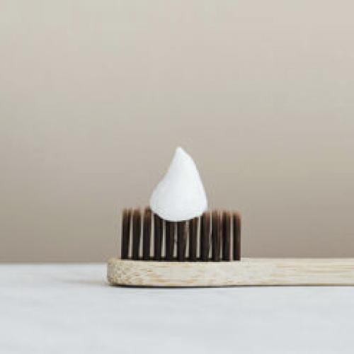 Handzahnbürste aus Holt liegt auf einem Marmorwaschtisch mit Zahnpasta.